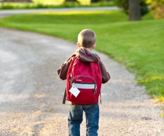 Kuvituskuvana pieni lapsi iso reppu selässä kävelemässä tiellä